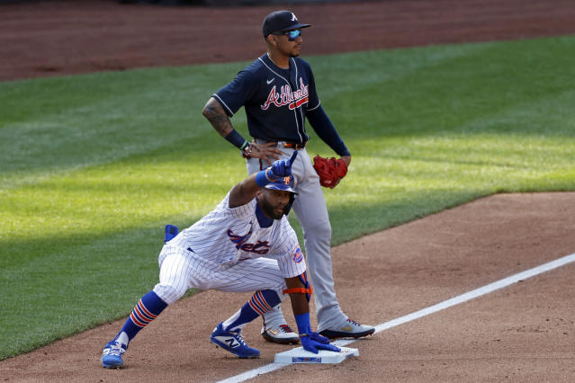 New York Mets' Amed Rosario, front, reacts in front of Atlanta Braves third baseman Johan Camargo after hitting an RBI-triple during the fifth inning of a baseball game Saturday, July 25, 2020, in New York. (AP Photo/Adam Hunger)