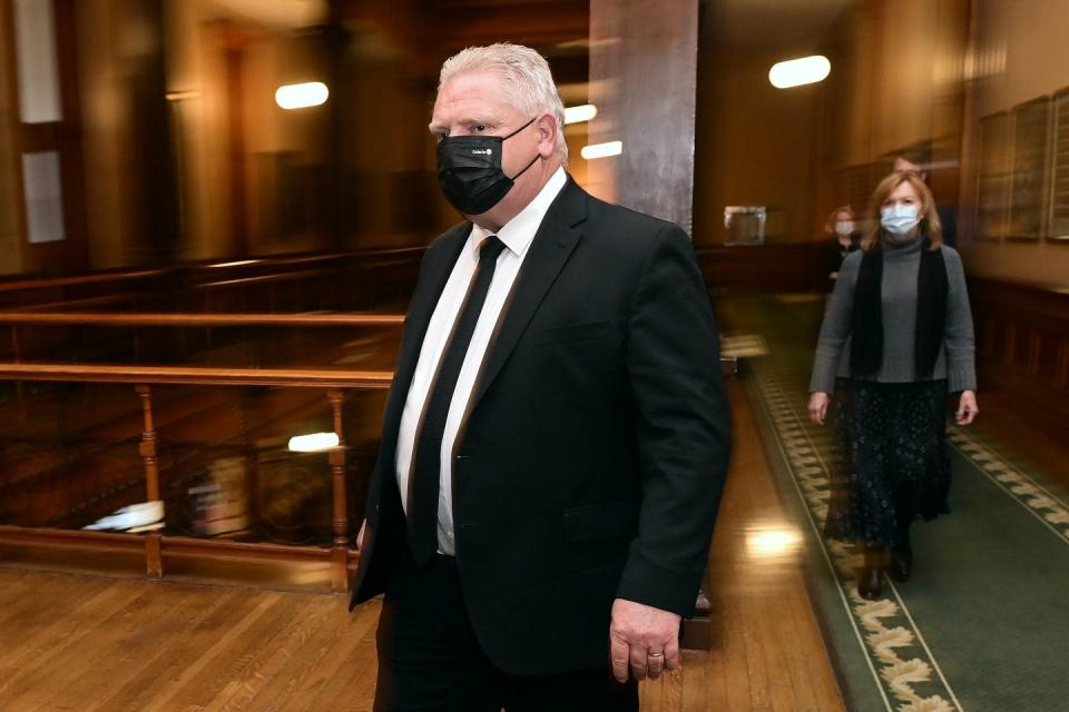 Premier Doug Ford wearing a black face mask, with Health Minister Christine Elliott in the background wearing a face mask.