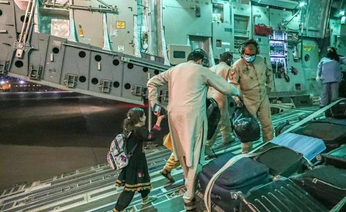 This undated handout picture provided by Qatar's Government Communications Office on August 21, 2021 shows evacuees from Afghanistan arriving at Al-Udeid airbase outside the capital Doha (AFP/-)