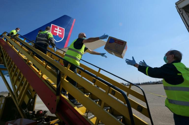 Police in Slovakia unload a plane after it touched down from China with testing kits and masks