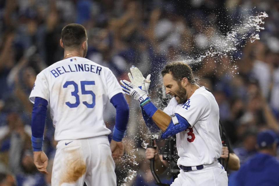 Los Angeles Dodgers' Chris Taylor (3) celebrates with Cody Bellinger (35) after they both scored off of a home run hit by Taylor during the ninth inning to win a National League Wild Card playoff baseball game 3-1 over the St. Louis Cardinals, Wednesday, Oct. 6, 2021, in Los Angeles. (AP Photo/Marcio Jose Sanchez)