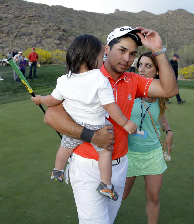 Jason Day, of Australia, holds his son Dash, as he walk off the green with his wife, Ellie, after winning his championship match against Victor Dubuisson, of France, during the Match Play Championship golf tournament on Sunday, Feb. 23, 2014, in Marana, Ariz. (AP Photo/Ted S. Warren)