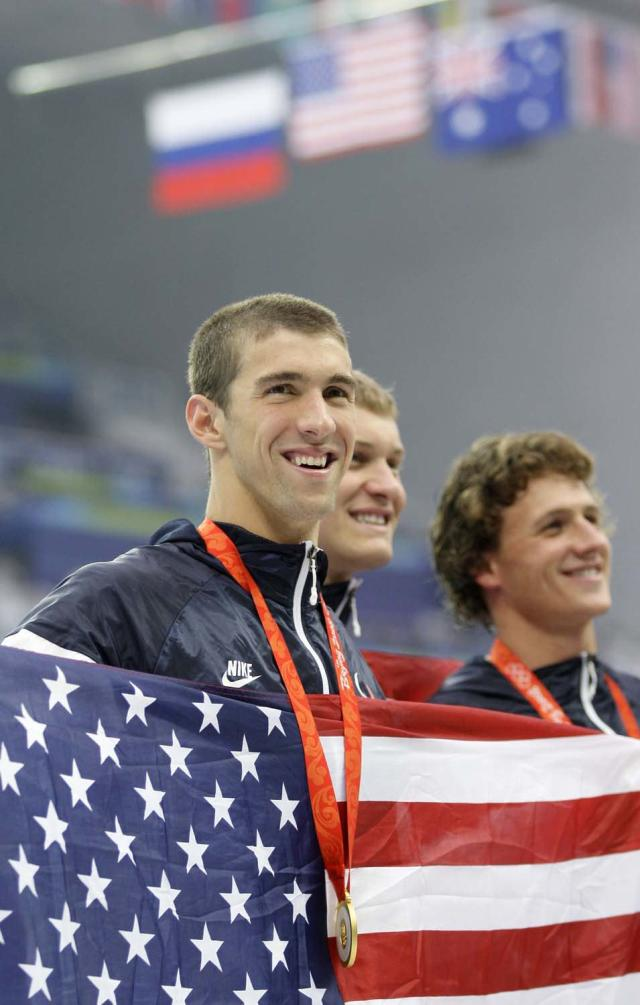 United States' gold medal winners, from left, Michael Phelps, Peter Vanderkaay and Ryan Lochte, hold an American flag after the medal ceremony for the men's 4x200-meter freestyle relay during the swimming competitions in the National Aquatics Center at the Beijing 2008 Olympics in Beijing, Wednesday, Aug. 13, 2008. (AP Photo/David J. Phillip)