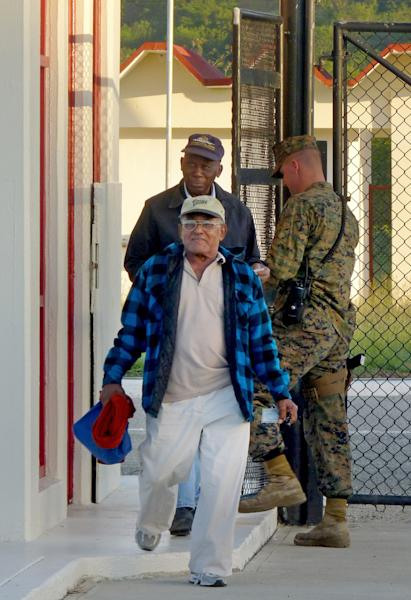 In this photo, Harry Henry, 82, back, and Luis La Rosa, 79, front, leave at the end of a working day at the U.S. base in Guantanamo, Cuba, Thursday, Dec. 13, 2012, where they have been working since they were in their late teens. La Rosa started working on the base at the age of 18 and Henry when he was 17. La Rosa and Henry, the last of what were once hundreds of Cubans commuting daily to work at the base, are retiring at the end of the December. (AP Photo/Suzette Laboy)