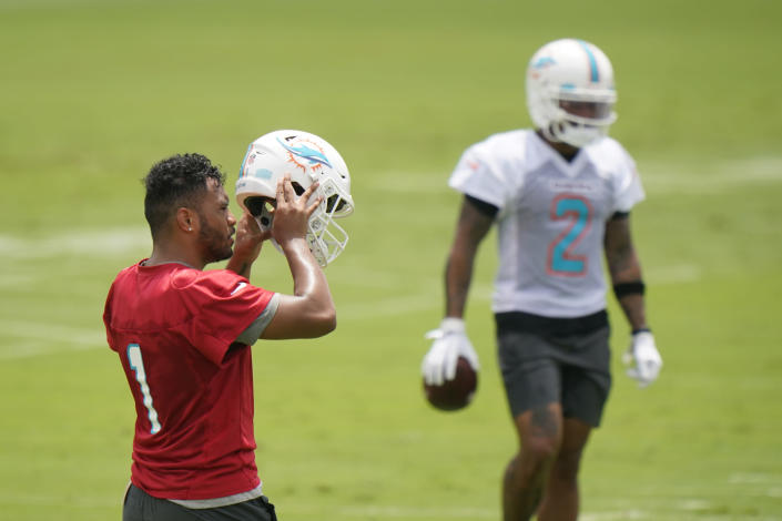 Miami Dolphins quarterback Tua Tagovailoa (1) takes off his helmet between drills during a mandatory minicamp at the NFL football team's training camp, Tuesday, June 15, 2021, in Davie, Fla. (AP Photo/Wilfredo Lee)