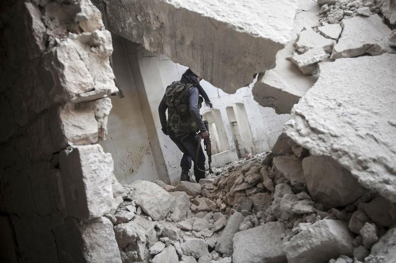 In this Friday, Nov. 02, 2012 photo, a rebel fighter walks among the debris of damaged residential buildings after several days of intense fighting between rebel fighters and the Syrian army in the Karm al-Jebel neighborhood in Aleppo, Syria. U.N. officials and human rights groups believe President Bashar Assad's regime is responsible for the bulk of suspected war crimes in Syria's 19-month-old conflict, which began as a largely peaceful uprising but has transformed into a brutal civil war. However a video that appears to show a unit of Syrian rebels kicking terrified, captured soldiers and then executing them with machine guns raised concerns Friday about rebel brutality at a time when the United States is making its strongest push yet to forge an opposition movement it can work with. (AP Photo/Narciso Contreras)