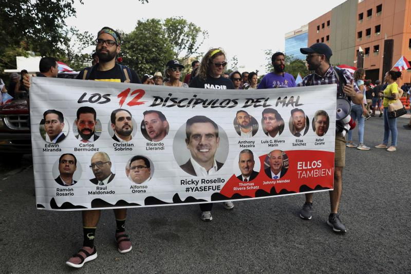 "Protesters hold a banner featuring resigned Gov. Ricardo Rosselló, center, amid other politicians that reads in Spanish ""The 12 disciples of evil. Them too."" as they demand the resignation of Justice Secretary Wanda Vazquez outside the Department of Justice in San Juan, Puerto Rico, Monday, July 29, 2019. Less than four days before Gov. Ricardo Rosselló steps down, no one knows who will take his place and his constitutional successor Wanda Vázquez said Sunday that she didn't want the job. (AP Photo/Brandon Cruz González)"