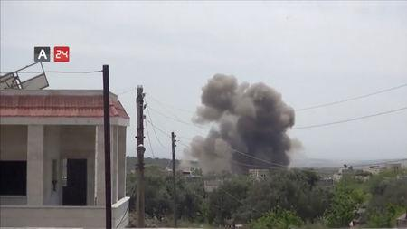 A barrel bomb dropped from a helicopter explodes in Karsaa, Idlib province