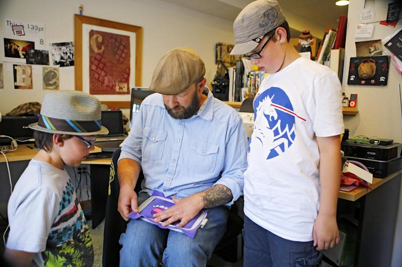 This photo taken on May 23, 2013 shows Ray Tollison inserting material into a frame for sewing, as sons Sam, left, and Ben look on at their home in Fort Collins, Colo. The Tollisons launched Monster to Love, a company that makes plush monster toys. (AP Photo/Ed Andrieski)