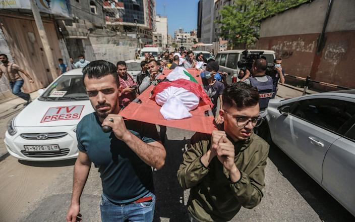 Palestinians carry the bodies of the Abu Hatab family during their funeral in Gaza City - Mohammed Talatene / Avalon