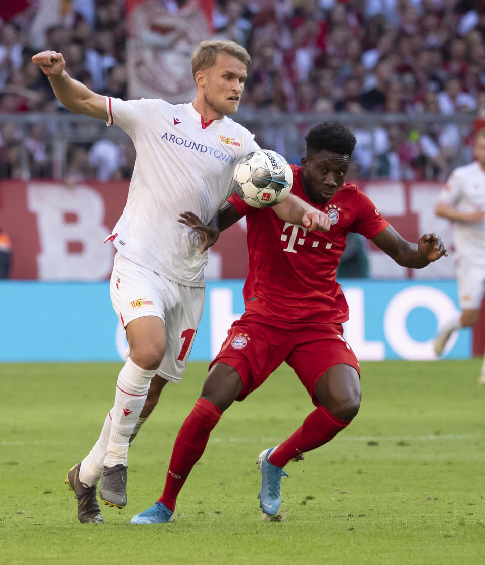 Munich's Alphonso Davies, right, challenges for the ball with Berlin's Sebastian Andersson, left, during the German Bundesliga soccer match between FC Bayern Munich and 1. FC Union Berlin in Munich, Saturday, Oct. 26, 2019. (Sven Hoppe/dpa via AP)