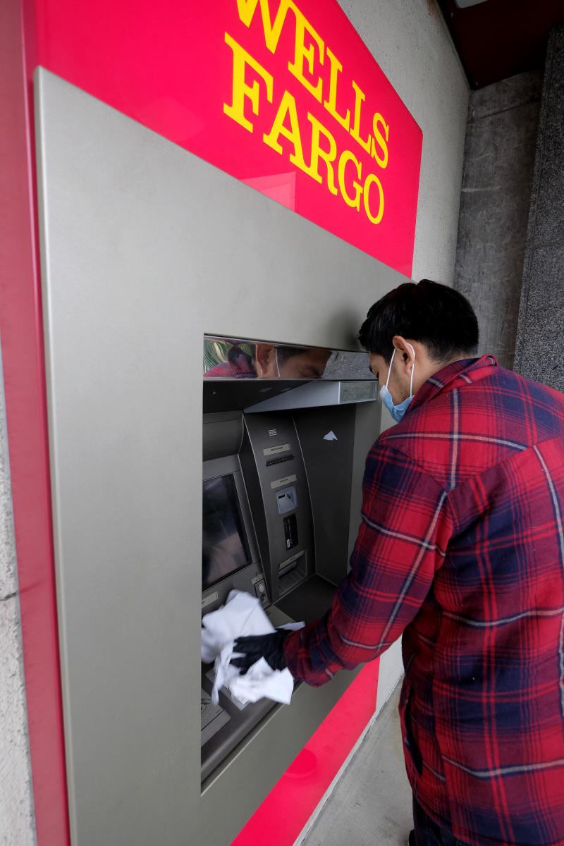 Alverick Guzman wearing a face mask cleans the ATM machine at a bank in Alhambra, Calif., Thursday, March 12, 2020. (AP Photo/Ringo H.W. Chiu)