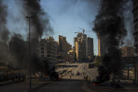 Protesters stand in front of burning tires set on fire to block a main road, after the Lebanese pound hit a record low against the dollar on the black market, in Beirut, Lebanon, Saturday, March 6, 2021. (AP Photo/Hassan Ammar)