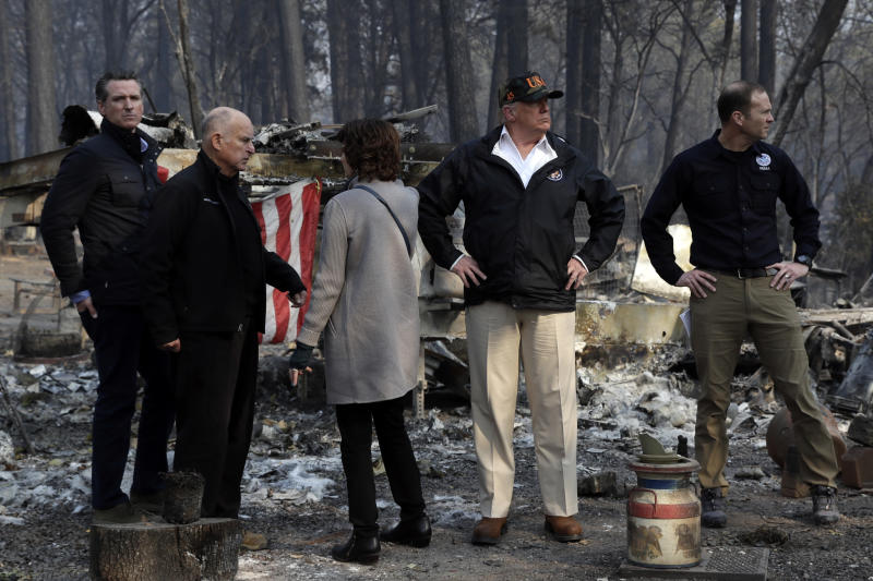 President Donald Trump talks with from left, Gov.-elect Gavin Newsom, California Gov. Jerry Brown, Mayor of Paradise Jody Jones and FEMA Administrator Brock Long during a visit to a neighborhood destroyed by the wildfires, Saturday, Nov. 17, 2018, in Paradise, Calif. (AP Photo/Evan Vucci)