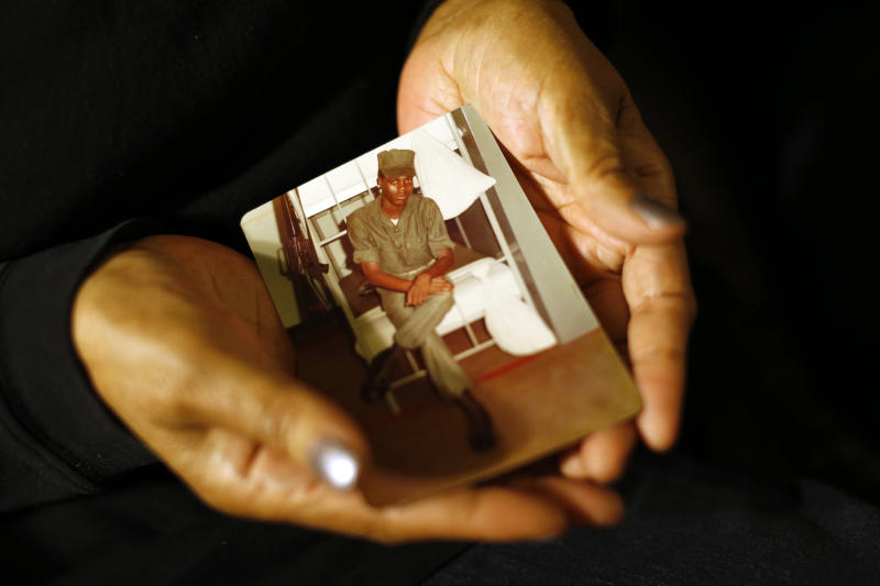 In this March 12, 2014 photo, Alma Murdough holds a photo of her son, Jerome, at her home in the Queens borough of New York. Jerome Murdough, a mentally ill, homeless former Marine arrested for sleeping in the roof landing of a New York City public housing project during one of the coldest recorded winters in city history, died last month in a Rikers Island jail cell that multiple city officials say was at least 100 degrees when his body was discovered. Murdough, 56, was found dead in his cell in a mental observation unit in the early hours of Feb. 15, after excessive heat, believed to be caused by an equipment malfunction, redirected it's flow to his upper-level cell, the officials said. (AP Photo/Jason DeCrow)