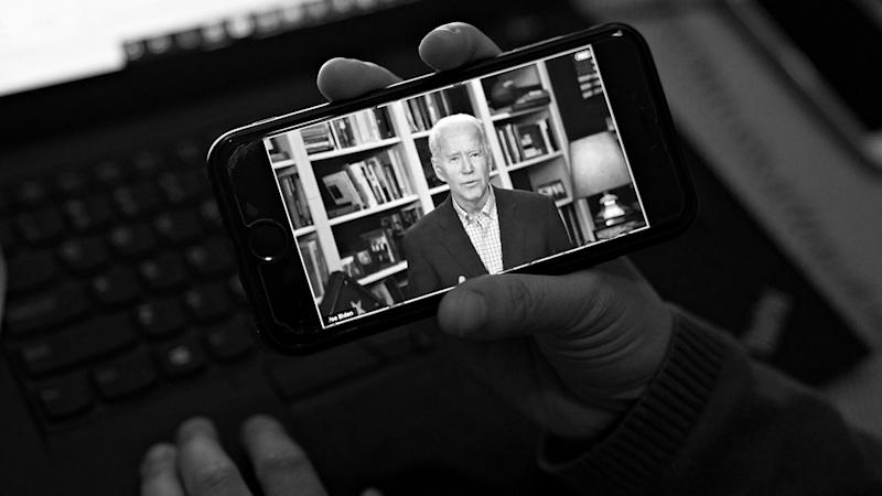 Former Vice President Joe Biden, 2020 Democratic presidential candidate, speaks during a virtual press briefing on a smartphone in this arranged photograph in Arlington, Virginia, U.S., on Wednesday, March 25, 2020. (Andrew Harrer/Bloomberg via Getty Images)