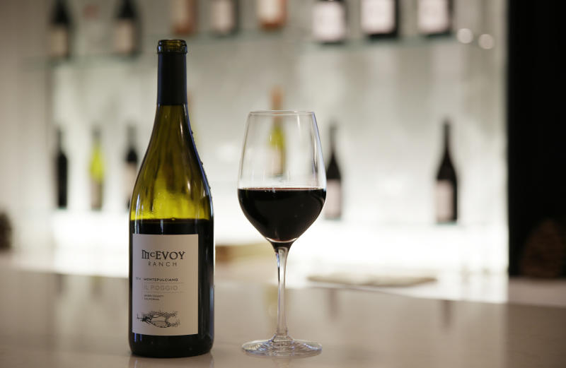 """In this photo taken Monday, May 21, 2018, a glass and bottle of McEvoy Ranch Il Poggio Montepulciano wine stand on a tasting room counter at the winery in Petaluma, Calif. The ranch is located in Northern California's Petaluma Gap which is one of America's newest viticultural areas. The area's slogan: """"From wind to wine."""" (AP Photo/Eric Risberg)"""