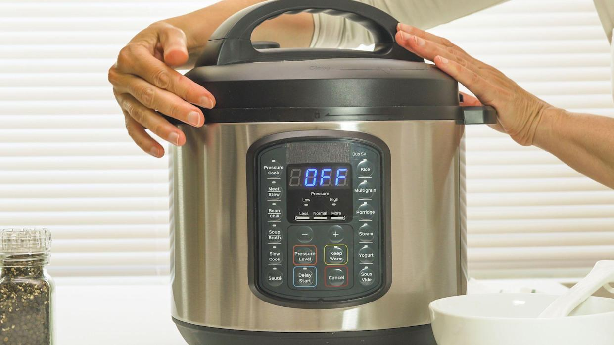 Multi cooker close up on kitchen table. Woman lifting the lid