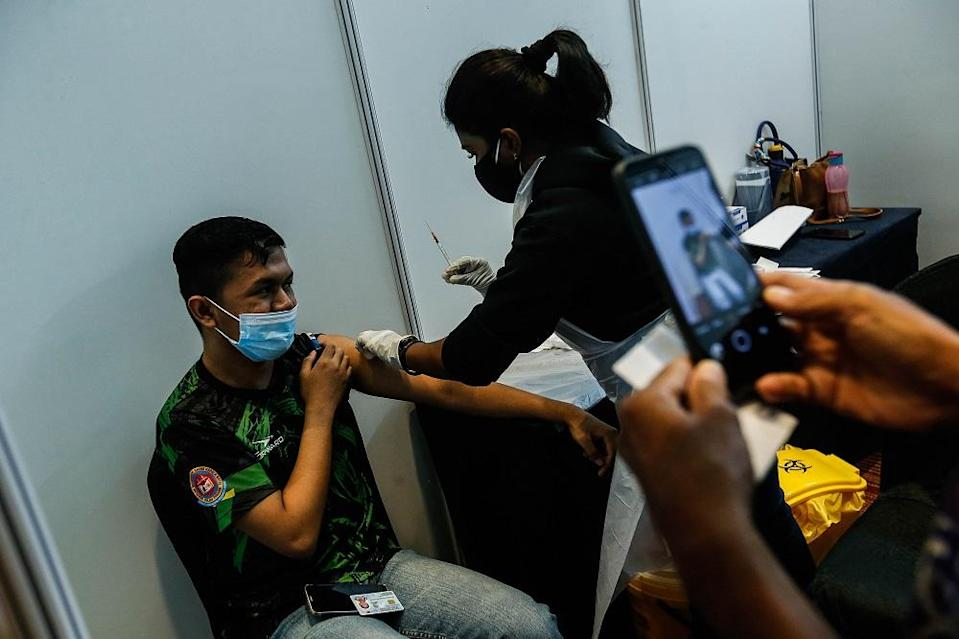 A teenager receives his Covid-19 vaccination shot at the Subterranean Penang International Convention and Exhibition centre in Bayan Baru September 22, 2021. Those in the 12 to 15 age group will begin their vaccinations on Wednesday. —Picture by Sayuti Zainudin
