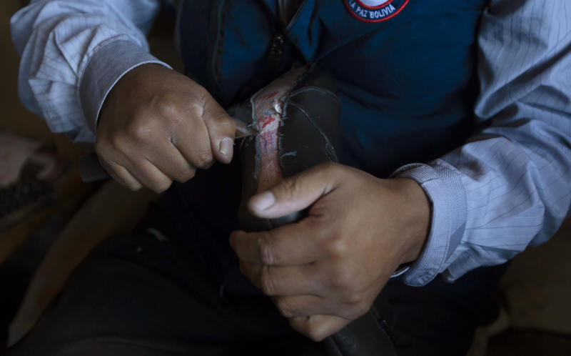 In this June 28, 2019 photo, Abraham Rodríguez works in his shoe shop in Villa Rosasani on the outskirts of La Paz, Bolivia. Rodríguez says the tax-free import of goods and the black market have affected his sales and have caused him to go into debt. (AP Photo/Juan Karita)