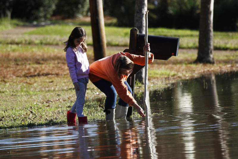 Barbara Beavers marks a pole used to measure the flooding on her street, as her granddaughter McRee Raggio, 7, checks to make sure the measuring is accurate in northeast Jackson, Miss., Friday, Feb. 14, 2020. As of Friday afternoon, the Pearl River was at 35.48 feet, which is more than 7 feet above flood stage. On Sunday, the river is expected to crest at 38 feet. Only twice before has the Pearl River surpassed 38 feet — during the historic floods of 1979 and 1983. (AP Photo/Rogelio V. Solis)