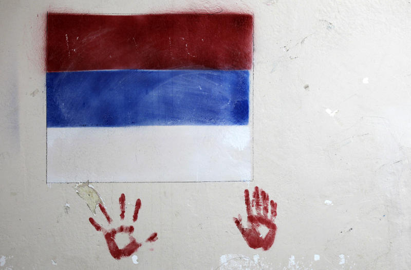 A Serbian flag is painted on a wall at a polling station in the northern Serb-dominated part of Mitrovica, Kosovo, Sunday, Nov 3, 2013. People in Kosovo are voting in a local election that will test the country's fragile relations with Serbia as both countries seek to move closer to the European Union. (AP Photo/Darko Vojinovic)