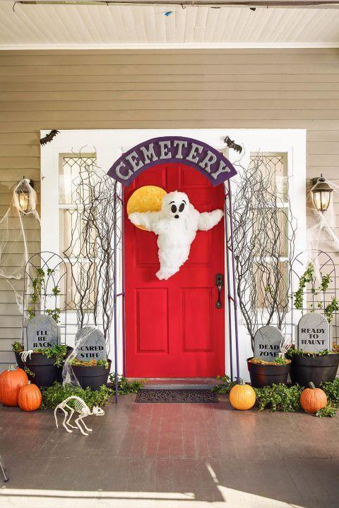"""<p>Create a creepy graveyard gate out of a metal garden arbor flanked by foam-kickboard gravestones. A DIY friendly ghost plus a skulking store-bought skeleton cat, skeleton arms, and rubber bats complete the scene.</p><p>GHOST</p><p>1. Sketch lower portion of ghost body onto white foam-core (it should be about 2' to 3' tall); cut out with utility knife.</p><p>2. On back of foam-core, position 2 skewers as base of arms; duct-tape in place. Duct-tape loop of monofilament at top for hanging.</p><p>3. To create head, wrap 4"""" foam ball in polyester batting until about 6"""" in diameter; secure with hot glue. Pierce ball with 3 skewers to create tripod, then poke other end of skewers into top of foam-core body; secure with hot glue.</p><p>4. Wrap more batting around foam-core body and skewers. To hold in place, lightly wrap with monofilament. Then, wrap batting around neck skewers to fill out ghost's body. Continue adding and fluffing batting until it feels full.</p><p>5. Cut eyes, eyebrows and mouth from black felt; attach with hot glue.</p><p>MOON</p><p>1. Push end of paintbrush into front of 15"""" foam disk to create various-size craters.</p><p>2. Mix together ½ cup light orange acrylic craft paint and ¼ cup flour. Add water or more flour for a paste-like consistency.</p><p>3. Spread flour/paint mixture over surface and sides of disk, covering (but not filling) craters; let dry.</p><p>4. Tie monofilament to thumbtack and press into back for hanging.</p><p>CEMETERY SIGN</p><p>1. Lay top piece of a 7' x 4' metal garden arch on top of 40"""" x 60"""" piece of black foam-core. Use ruler to measure 5"""" above and 5"""" below arbor arch, marking foam-core with a pencil every few inches to replicate arch shape. (To check size, place 6"""" wooden craft letters to spell <em>CEMETERY</em> on foam-core arch.) Connect marks, then cut out arch with utility knife; smooth ragged edges with sandpaper.</p><p>2. Apply purple spray paint to foam-core arch and stone spray paint to letters; let dry. Hot-glu"""