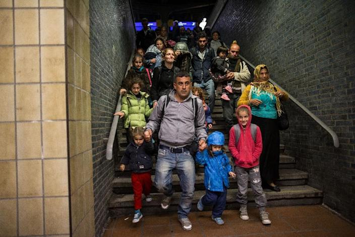 Refugees walk down the stairs after arriving at a railway station in Dortmund, western Germany, on September 13, 2015 (AFP Photo/Maja Hitju)