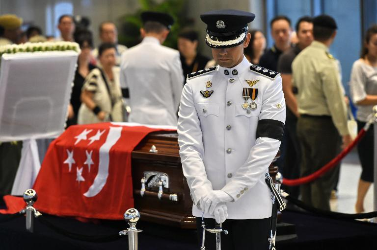 A Singapore policeman holds his post as mourners pay their respects to Singapore's late former prime minister Lee Kuan Yew as he lies in state at Parliament House ahead of his funeral on March 26, 2015