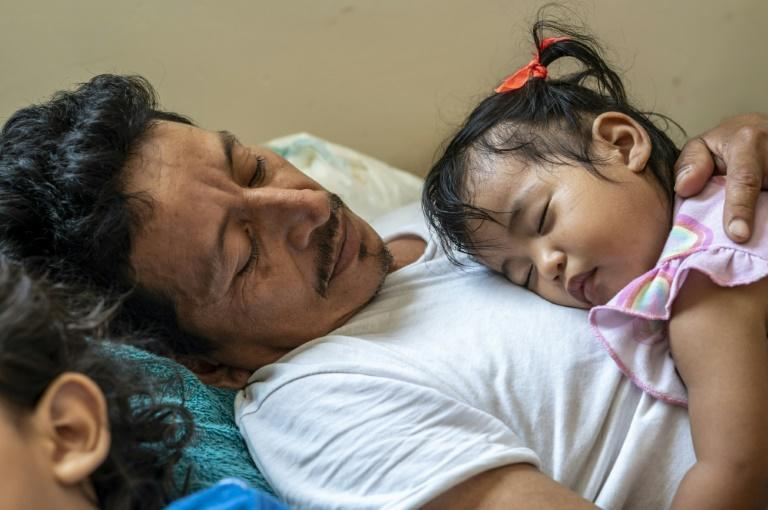 Safe haven: Migrant Jose Eliberto Hernandez Lopez lays down with his daughter Enya on his chest and his son Jose next to him at a shelter in Matamoros, Mexico