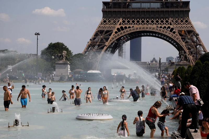 People cool off in the Trocadero fountains near the Eiffel Tower in Paris (REUTERS)