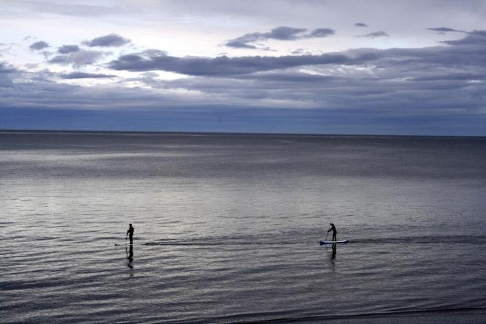 """In this May 25, 2015, photo people use paddle boards in Kachemak Bay in Homer, Alaska. Homer is wading deeper into the national political debate, becoming the latest U.S. city to consider affirming its commitment to inclusion amid concerns about the treatment of immigrants, religious groups, the LGBTQ community and others. The City Council on Monday, Feb. 27, 2017, is expected to weigh a resolution that states Homer will resist any efforts to profile """"vulnerable populations"""" and will reject any expressions of fear and hate. (AP Photo/Mark Thiessen)"""