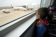 Yancarlos Amaya, 5, a migrant from Honduras, looks out at a United Airlines regional jet that will transport him and his mother, Celestina Ramirez, at Valley International Airport, Wednesday, March 24, 2021, in Harlingen, Texas. The mother and son, who were headed to Baltimore to reunite with Ramirez's brother, were allowed to stay in the U.S. after turning themselves in to U.S. Customs and Border Protection upon crossing the border. (AP Photo/Julio Cortez)