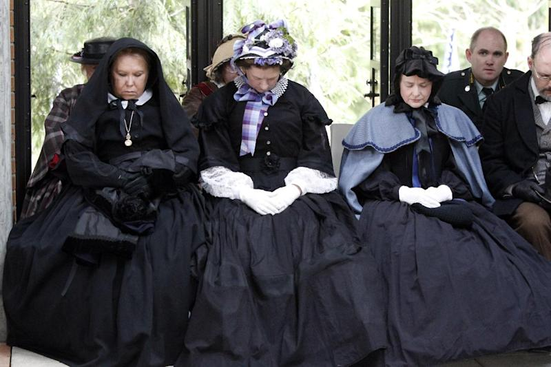 Women in period dress pray during the  military funeral for Civil War veteran Peter Knapp at Willamette National Cemetery in Portland, Ore., Friday, April 13, 2012.  Knapp is the first Civil War veteran buried at Willamette National Cemetery, Oregon's largest veterans' cemetery. His ashes had been sitting on a shelf at the Portland Crematorium since 1924.(AP Photo/Don Ryan)