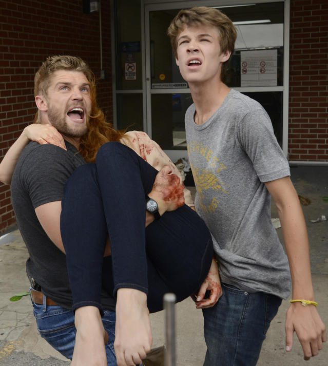 """""""Speak of the Devil"""" - Joe (Colin Ford) helps Barbie (Mike Vogel) brings Julia (Rachelle Lefevre) to the clinic when she is wounded on """"Under the Dome."""""""