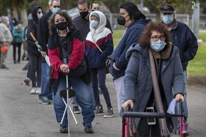 ENCINO, CA - JANUARY 27, 2021:Valerie Dunlap, 67, left, of Granada Hills, and Cookie Lewis, 68, right, of Valley Village, make their way with others in the by appointment only line to get vaccine shots to protect against the coronavirus at the Balboa Sports Complex in Encino. (Mel Melcon / Los Angeles Times)