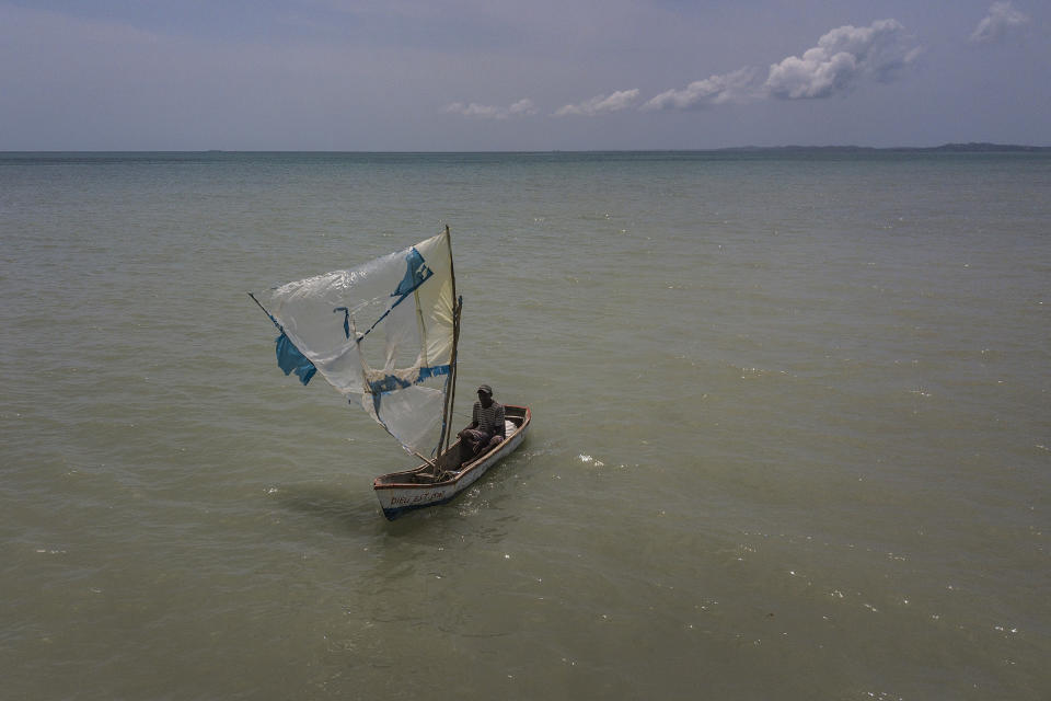 A fisherman navigates his boat with a broken sail made of recycled plastic as he returns to shore in Les Cayes, Haiti, Friday, Aug. 20, 2021, six days after a 7.2 magnitude earthquake hit the area. (AP Photo/Matias Delacroix)