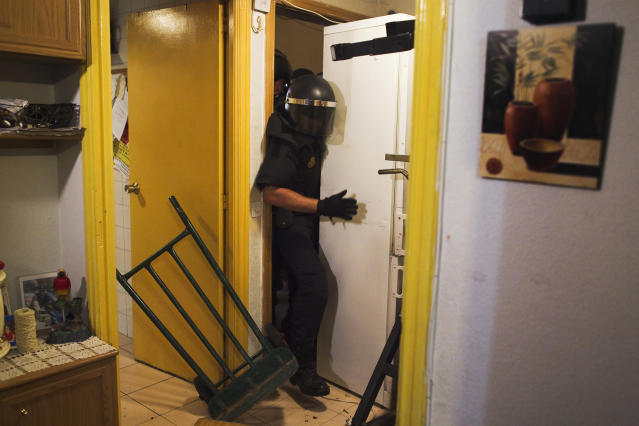<p>Police remove the door and push away a refrigerator as they break into Maria Isabel Rodriguez Romero's apartment to evict her and her family in Madrid, Sept. 25, 2013. (AP Photo/Andres Kudacki) </p>