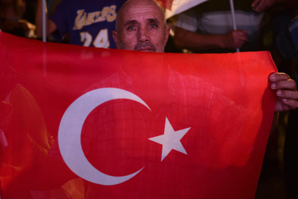 A supporter of the newly elected Turkish Cypriot leader Ersin Tatar holds a Turkish flag and celebrates, in the Turkish occupied area in the north part of the divided capital Nicosia, Cyprus, Sunday, Oct. 18, 2020. Ersin Tatar, a hardliner who favors even closer ties with Turkey and a tougher stance with rival Greek Cypriots in peace talks has defeated the leftist incumbent in the Turkish Cypriot leadership runoff. (AP Photo/Nedim Enginsoy)