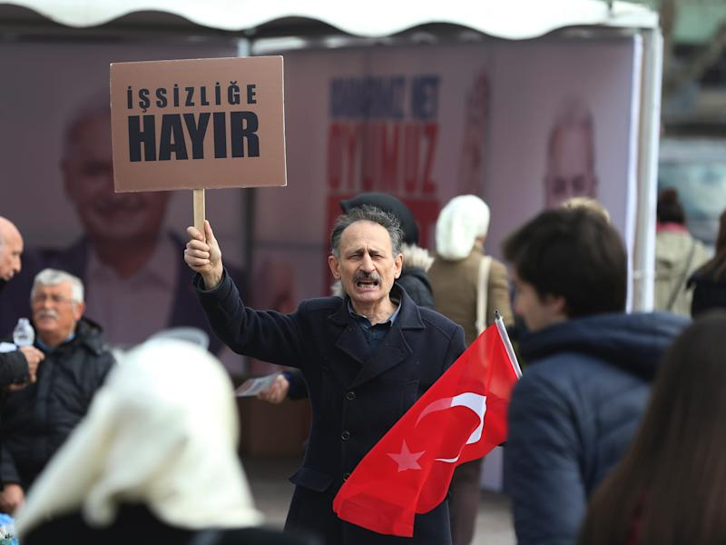 A Turkish man supporting the 'NO' vote for the upcoming referendum, holds a Turkish flag and a placard, reading in Turkish: 'No to unemployment', in Istanbul, Wednesday, March 15, 2017. Turkey is set to hold a referendum on April 16, 2017, on switching to a presidential system _ a move critics fear will concentrate too many powers in the hands of President Recep Tayyip Erdogan. (