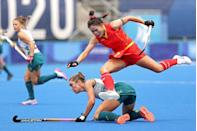 <p>Qiuxia Cui of China leaps over Grace Stewart of Australia during the women's preliminary field hockey match. </p>