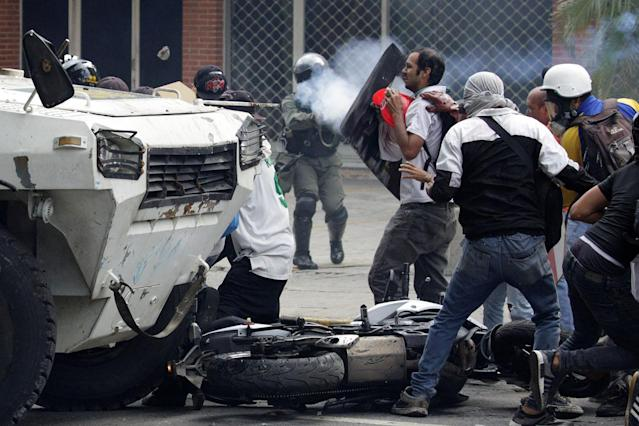 <p>Opposition supporters clash with riot police during a rally against President Nicolas Maduro in Caracas, Venezuela, Venezuela May 3, 2017. (Marco Bello/Reuters) </p>