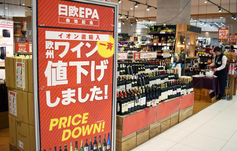 """Bottles of wine imported from Europe are lined up at a retail store in Chiba, near Tokyo, Friday, Feb. 1, 2019. The European Union and Japan have inaugurated a landmark deal they say will boost trade between the two economic powers and sends the message that international agreements still have a purpose in an age of increasing protectionism. The agreement that comes into effect Friday will scrap nearly all tariffs on products both sides trade in. The banner at left reads: """"European wine was priced down!"""" (Kyodo News via AP)"""