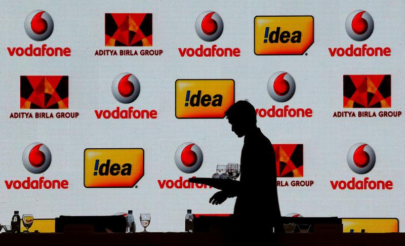 FILE PHOTO: A hotel employee clears a table after Vodafone Group and Idea Cellular news conference in Mumbai