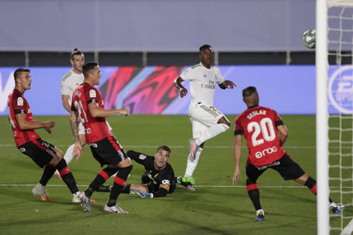 Real Madrid's Vinicius Junior, second right, kicks the ball to scoring the opening goal during the Spanish La Liga soccer match between Real Madrid and Mallorca at Alfredo di Stefano stadium in Madrid, Spain, Wednesday, June 24, 2020. (AP Photo/Bernat Armangue)