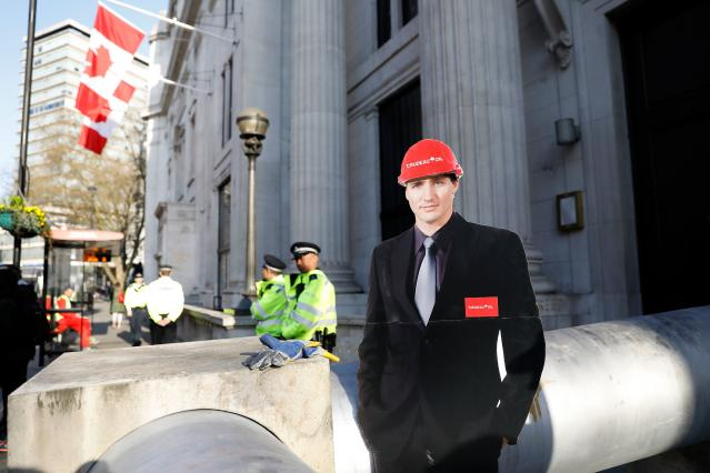 A cardboard cut-out of Canada's Prime Minister Justin Trudeau is pictured as demonstrators use a mock oil pipeline to block the entrance to the Canadian Embassy in central London on April 18, 2018. (Photo credit should read TOLGA AKMEN/AFP/Getty Images)