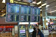 Passengers check flight information display boards at Singapore Changi airport terminal on December 28, 2014