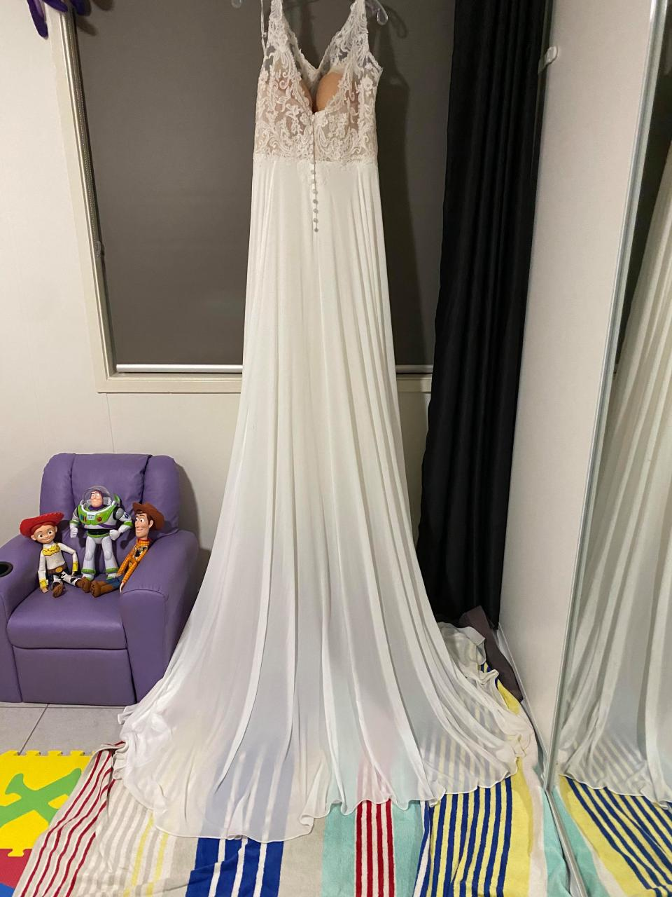 Image of clean wedding gown hanging in lounge room