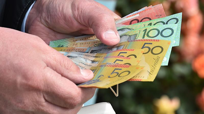 World Health Organisation has warned the coronavirus could spread through bank notes. Pictured is a man's hands holding Australian currency.
