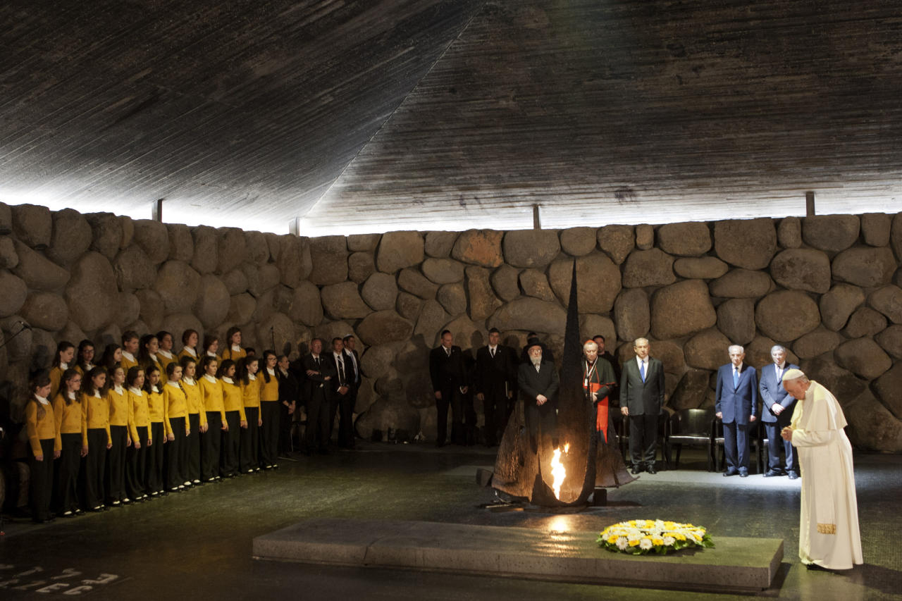 Pope Francis lays a wreath as Israel's President Shimon Peres and Israeli Prime Minister Benjamin Netanyahu stand at the Hall of Remembrance at the Yad Vashem Holocaust memorial in Jerusalem, Monday, May 26, 2014. Francis honored Jews killed in the Holocaust and in terrorist attacks, and kissed the hands of Holocaust survivors as he capped his three-day Mideast trip with poignant stops Monday at some of the holiest and most haunting sites for Jews. (AP Photo/Dan Balilty)